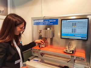 Not a drop too much in the textile: Liebherr worker Laura Zell explains the sensor on textile moisture-measurement unit.
